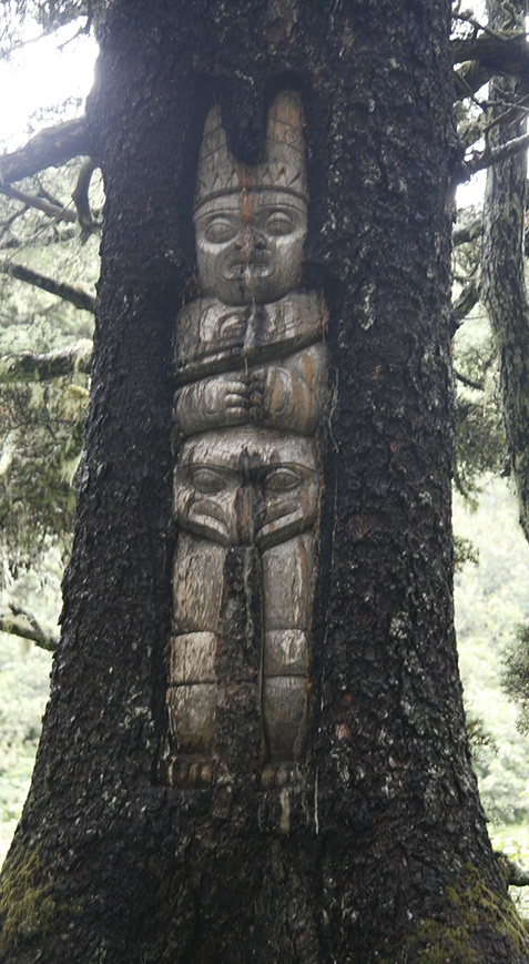 an unusual Totem Pole carved into a tree.